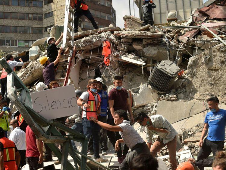Les secouristes affichent une lecture de placard & Silence & # 39; Alors qu'ils se dépêchent de libérer des victimes possibles des décombres d'un bâtiment effondré après un tremblement de terre qui a secoué la ville de Mexico le 19 septembre 2017