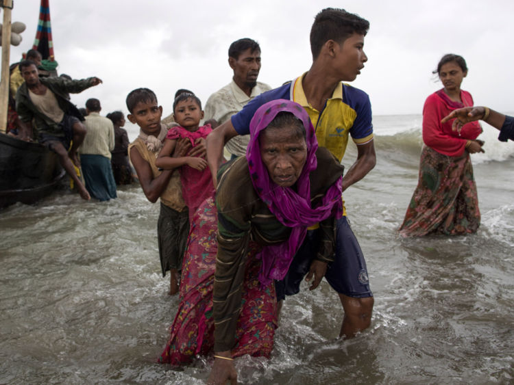 Un homme Rohingya aide une femme âgée hors de l'eau après son arrivée à Dakhinpara, au Bangladesh
