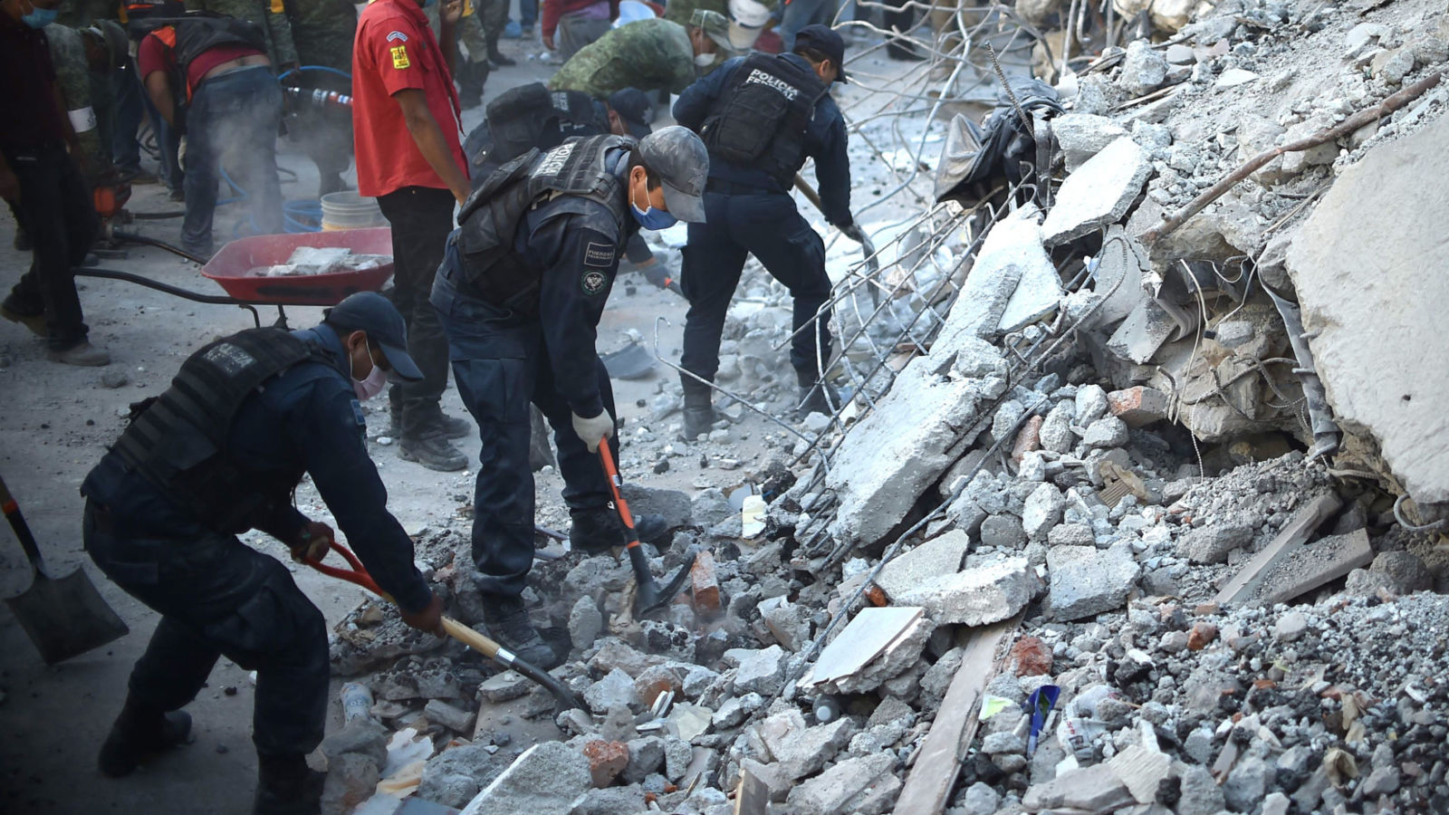 Les secouristes, les pompiers, les policiers, les soldats et les volontaires enlèvent les débris et les débris d'un bâtiment aplati