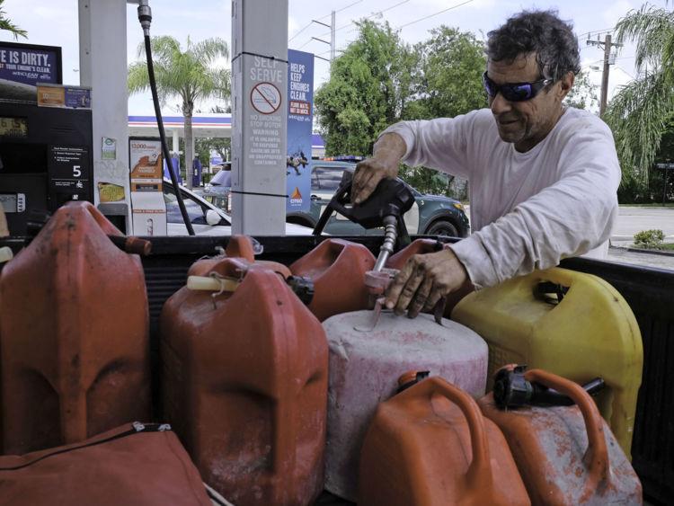 Robert Johnson remplit des conteneurs de gaz dans une station-service à Miami, en Floride, le 8 septembre 2017, devant l'ouragan Irma. Le gouverneur de la Floride, Rick Scott, a prévenu que tous les 20 millions d'habitants de l'État devraient être prêts à évacuer alors que l'ouragan Irma se débrouille pour un coup direct sur le sud des États-Unis. / AFP PHOTO / Gaston De Cardenas (Le crédit photo doit être lu GASTON DE CARDENAS / AFP / Getty Images)