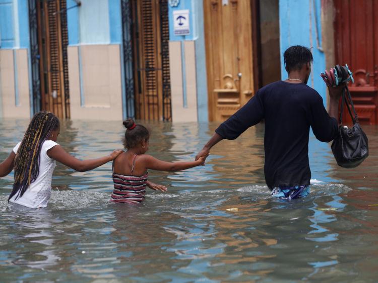 Un homme traverse une rue inondée de la Havane avec ses enfants