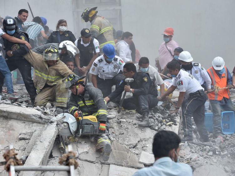Les secouristes, les pompiers, les policiers, les soldats et les volontaires enlèvent les débris et les débris d'un bâtiment aplati à la recherche de survivants après un puissant tremblement de terre à Mexico le 19 septembre 2017
