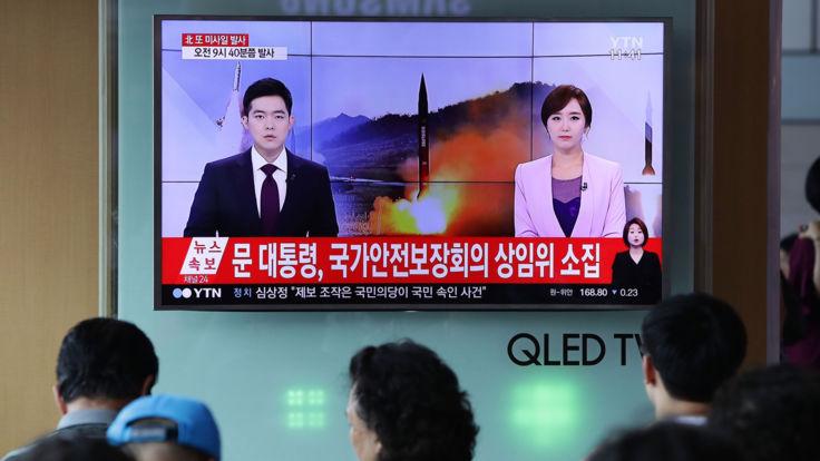 Les gens regardent les rapports télévisés sud-coréens du lancement ICBM