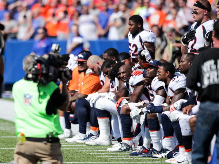 Les joueurs de Broncos de Denver s'agenouillent pendant l'hymne national américain avant un match de NFL contre Buffalo Bills