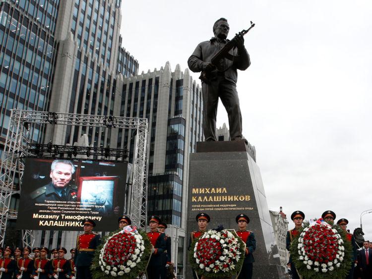 Les gardes d'honneur se tiennent à côté d'un monument à Mikhail Kalashnikov