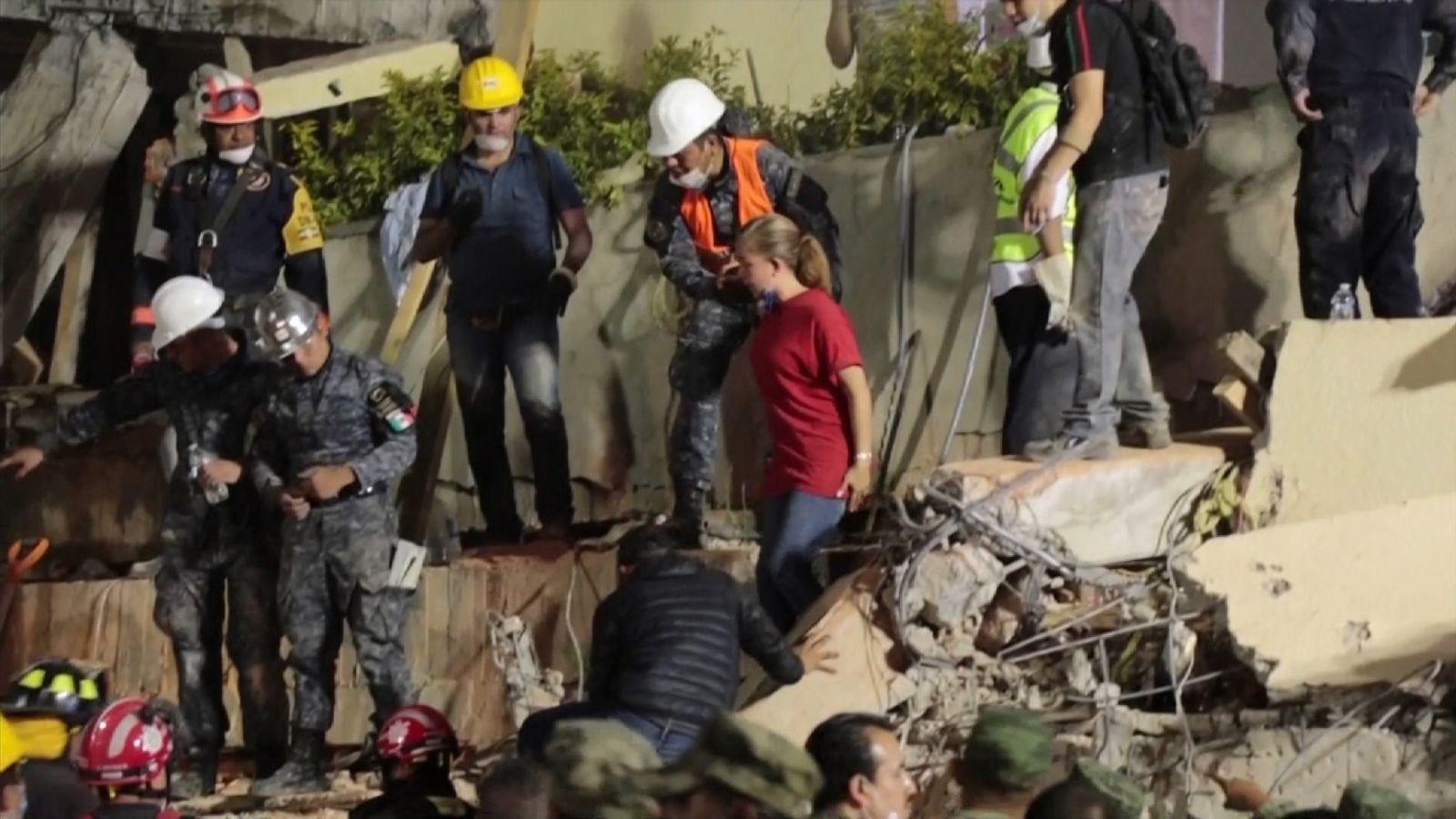 Une femme (T-shirt rouge) est aidée loin de l'école après avoir été invitée à identifier un corps
