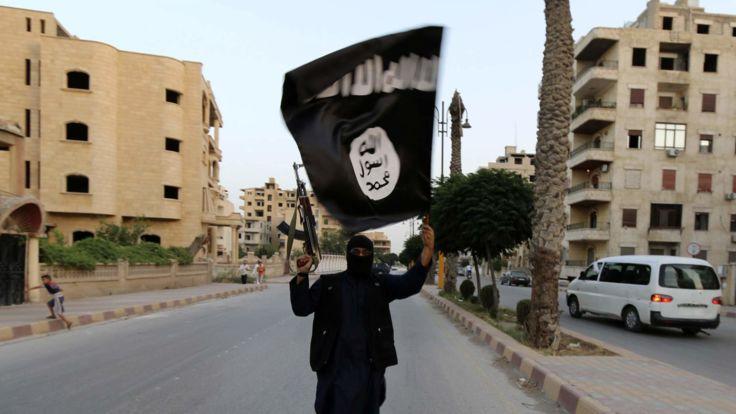 Un membre fidèle à l'ISIL brandit un drapeau de l'EIIL à Raqqa, en Syrie