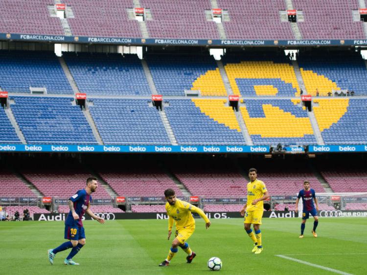 Lionel Messi joue le ballon devant un vide Nou Camp après une décision a été prise de jouer à huis clos