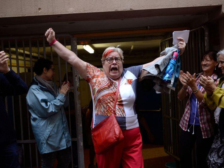 Une femme fête dehors un bureau de scrutin après avoir voté à Barcelone