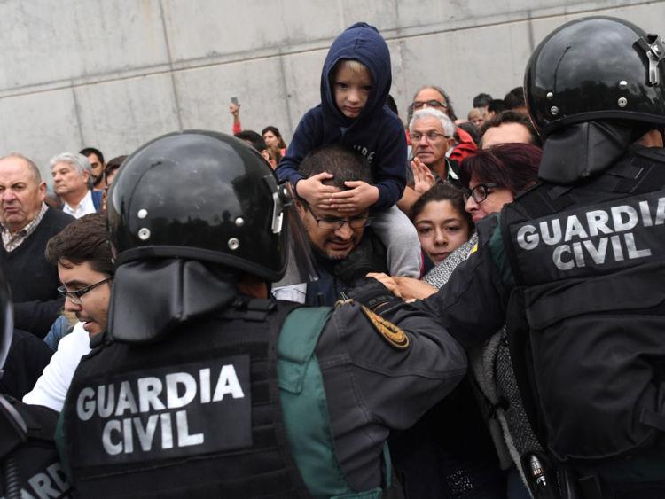 Un enfant est assis sur les épaules d'une personne alors que la police se déplace sur les foules