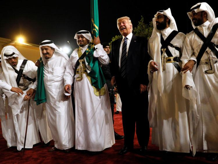 M. Trump danse avec une épée alors qu'il arrive à une cérémonie de bienvenue par le roi Salman