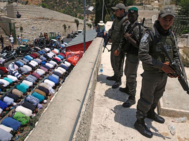 Les forces de sécurité israéliennes montent la garde alors que les fidèles musulmans palestiniens prient devant la Porte des Lions, une entrée principale de la mosquée Al-Aqsa dans la vieille ville de Jérusalem