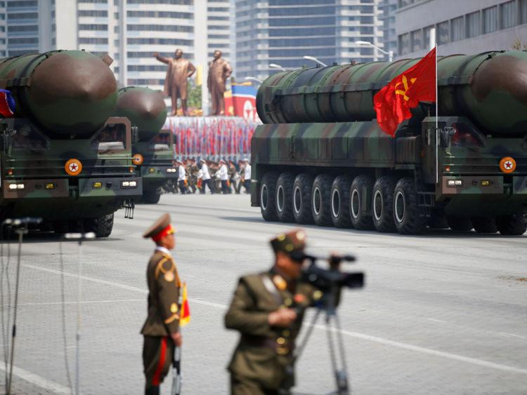 PHOTO DU FICHIER: Les missiles balistiques intercontinentaux (ICBM) passent le stand avec le dirigeant nord-coréen Kim Jong Un et d'autres hauts responsables lors d'un défilé militaire marquant le 105e anniversaire de naissance du père fondateur du pays, Kim Il Sung, à Pyongyang le 15 avril 2017. Les missiles eux-mêmes ont été montrés pour la première fois Le temps passé à l'intérieur d'un nouveau type de lanceur à cartouche samedi