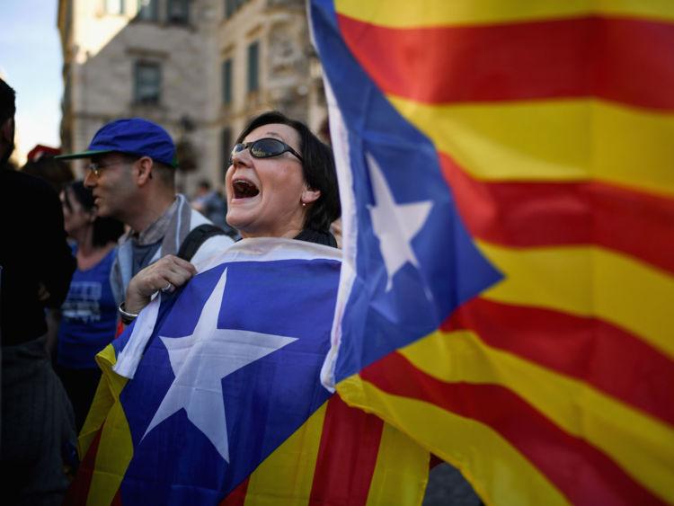 Des drapeaux séparatistes catalans sont brandis devant le Palais de la Generalitat à Barcelone