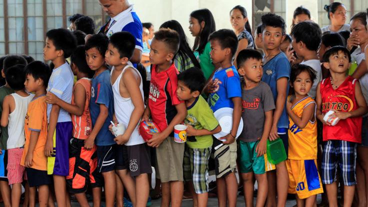Les enfants s'alignent pour des collations dans un centre d'évacuation