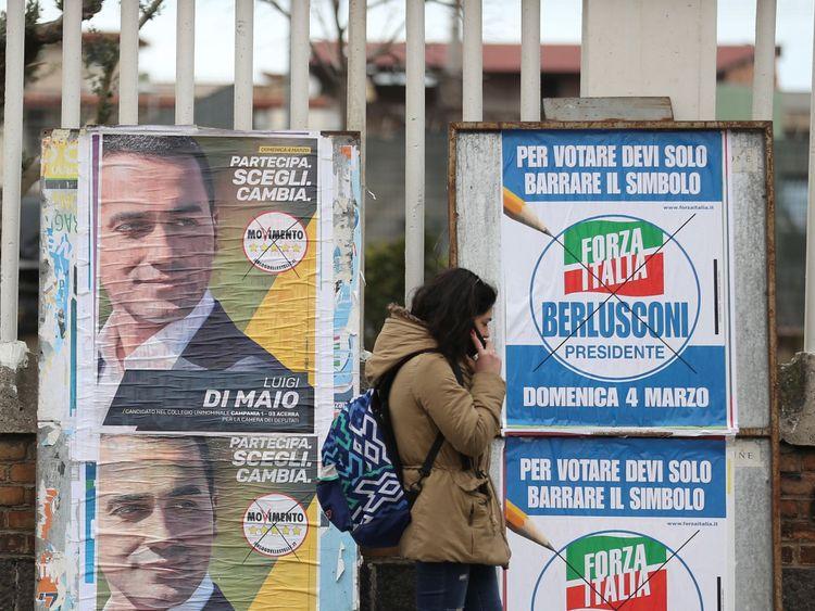 Une femme passe des affiches électorales à Naples avant l'ouverture du scrutin