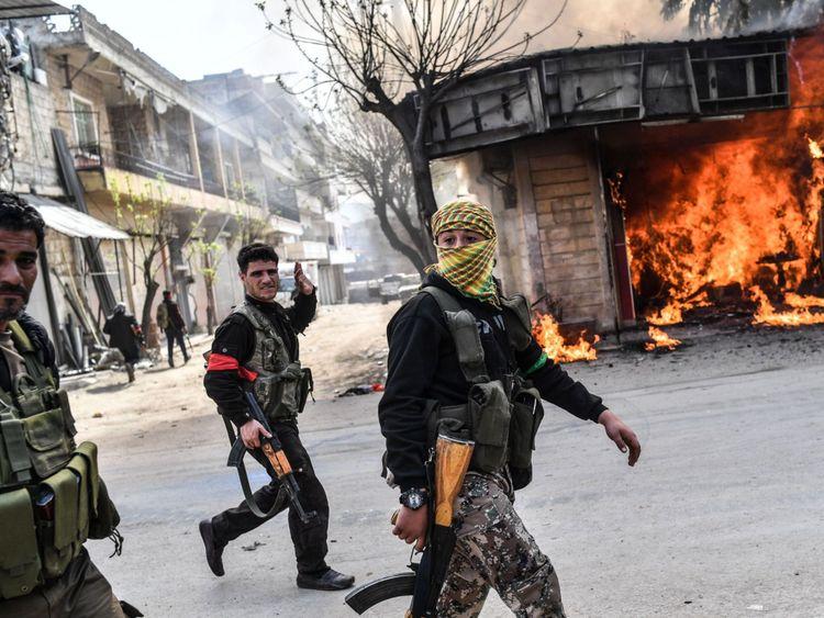 Les rebelles syriens soutenus par la Turquie passent devant un magasin en feu à Afrin