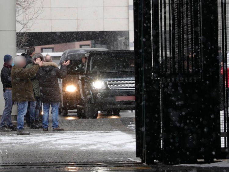 Des membres du personnel de l'ambassade britannique applaudissent alors qu'un convoi de véhicules quitte son complexe à Moscou
