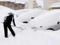 Une femme enlève la neige de sa voiture à Saint-Chaffrey, France
