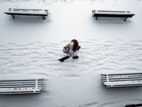 Une femme passe devant des bancs couverts de neige dans un parc à Lausanne, Suisse