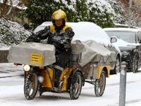 Une posteuse de l'opérateur suisse de courrier Schweizerische Post monte son trike électro dans une rue enneigée de Zurich , Suisse