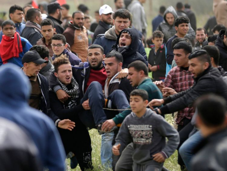 Un adolescent palestinien blessé est porté par d'autres manifestants alors qu'ils fuient lors d'affrontements