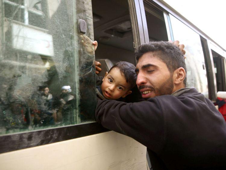 Un homme embrasse un enfant alors qu'il est évacué de l'Est Ghouta </span><br />         <span class=