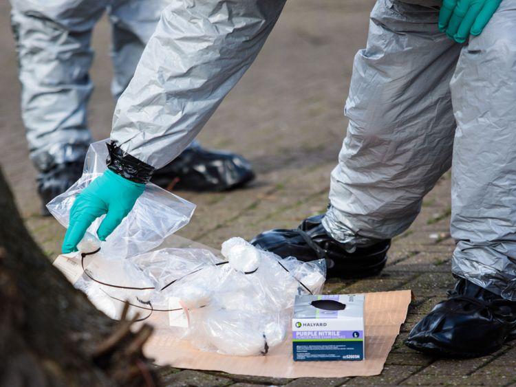 Les policiers en tenue de protection et les masques recueillent des échantillons près du banc où ils ont été trouvés