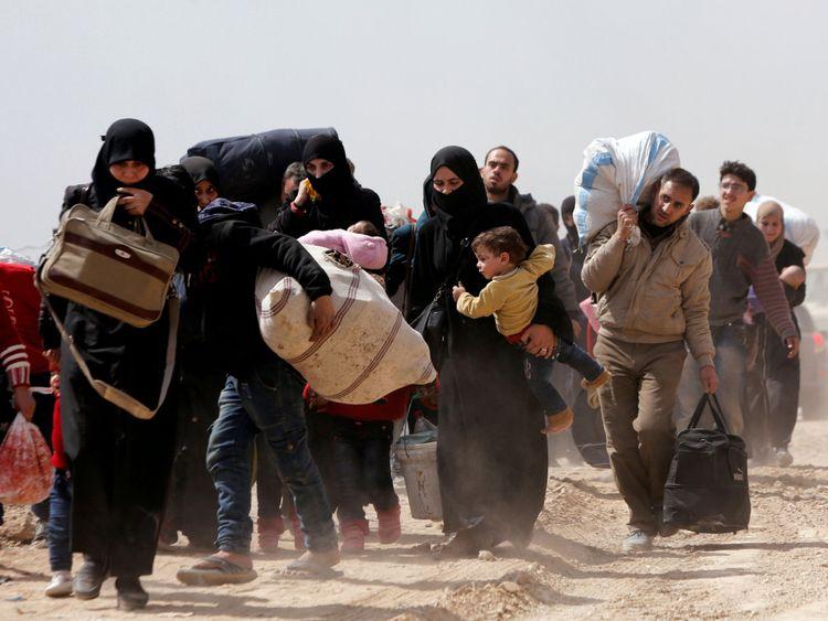 Les gens marchent avec leurs affaires alors qu'ils fuient la ville rebelle de Hammouriyeh, Ghouta orientale
