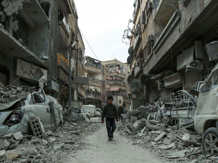 Une photo prise le 8 mars 2018 montre un chi syrien ld marchant dans une rue au-dessus des décombres des bâtiments détruits, dans la ville rebelle de Douma dans l'enclave de la Ghouta orientale à la périphérie de Damas