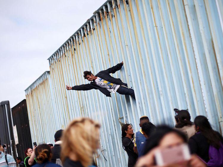 Un homme grimpe la barrière frontalière à l'appui des centaines de migrants centraméricains