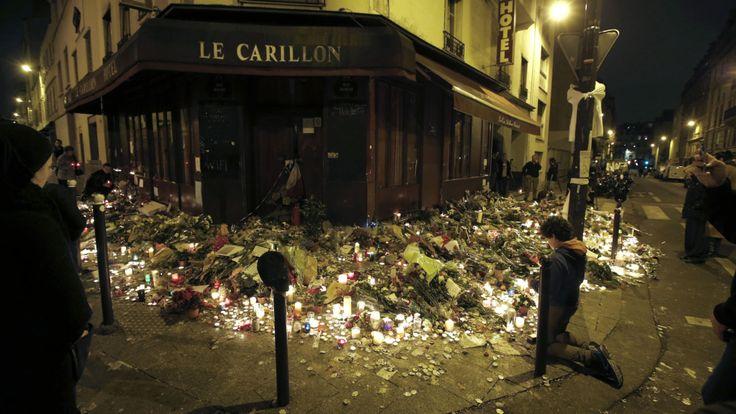 Des gens prient devant le restaurant Le Carillon, l'un des lieux d'attaque à Paris