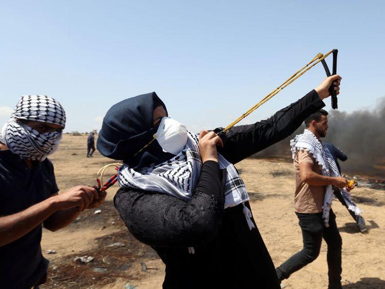Une femme utilise une fronde pour lancer des pierres sur les forces israéliennes