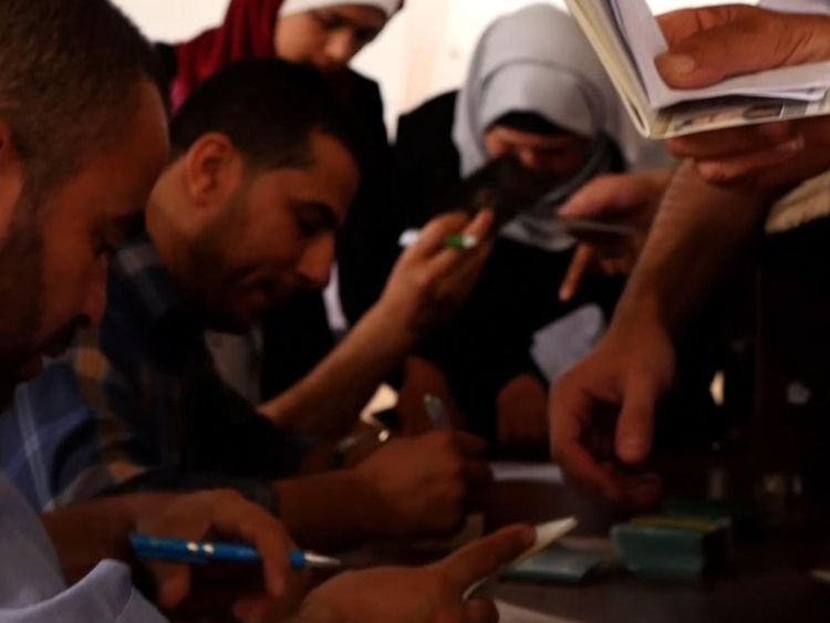 Les Palestiniens essaient de mettre de l'ordre dans leurs documents pour pouvoir monter dans un bus en Egypte
