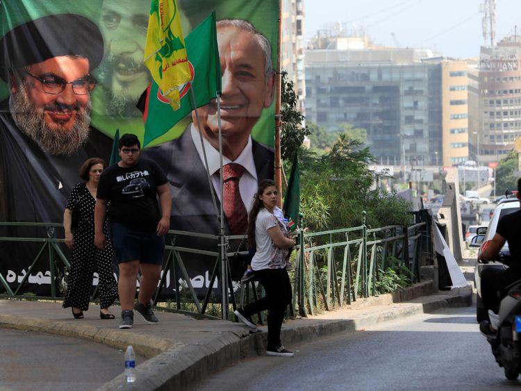Les gens passent devant une bannière de campagne montrant le président du Parlement libanais et candidat aux élections législatives Nabih Berri et le leader du Hezbollah Sayyed Hassan Nasrallah à Beyrouth, au Liban, le 4 mai 2018. REUTERS / Jamal Saidi