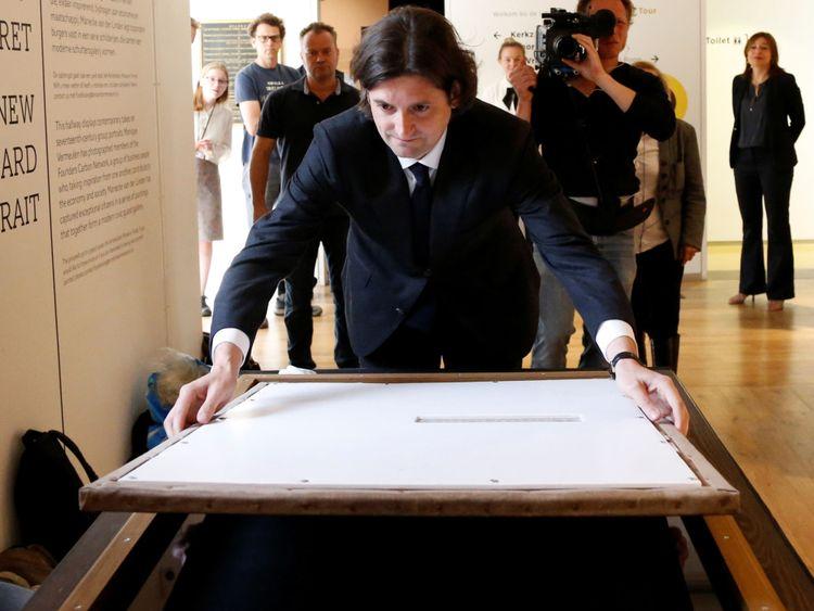 """Jan Six place un tableau de Rembrandt intitulé """"Portrait d'un jeune homme"""" dans son cadre à Hermitage Amsterdam"""