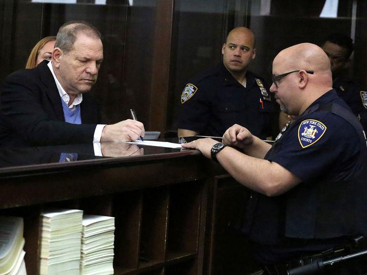Producteur de film Harvey Weinstein signe des papiers à l'intérieur du tribunal pénal de Manhattan lors de sa comparution à Manhattan à New York