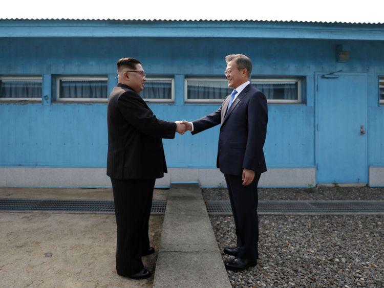 Kim Jong Un ( L) et Moon Jae-in (R) se serrent la main sur la ligne de démarcation militaire
