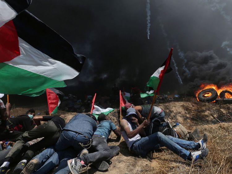 Des manifestants palestiniens se protègent du gaz israélien lors d'une manifestation contre l'ambassade des Etats-Unis à Jérusalem et devant le 70ème anniversaire de la Nakba, à la frontière entre Israël et Gaza dans le sud de la bande de Gaza. 14, 2018