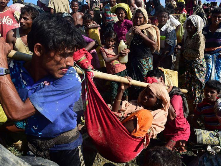 Les réfugiés rohingyas transportent une femme après avoir traversé la rivière Naf alors qu'ils fuient la violence au Myanmar pour atteindre le Bangladesh à Palongkhali près d'Ukhia le 16 octobre 2017. L'ONU a déclaré que 537 000 Rohingyas sont arrivés Bangladesh au cours des sept dernières semaines. Ils fuient la violence dans l'État de Rakhine, au Myanmar, où les Nations Unies accusent les troupes de mener une campagne de nettoyage ethnique contre eux. / PHOTO AFP / MUNIR UZ ZAMAN (Crédit photo devrait lire MUNIR UZ ZAMAN / AFP / Getty Images) </span><br />         <span class=