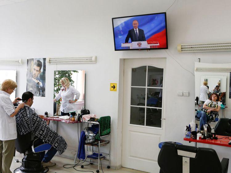 Un coiffeur assiste à l'inauguration de Vladimir Poutine. Président de la Russie, se reflète dans un miroir dans un salon de coiffure à Stavropol, en Russie 7 mai 2018. REUTERS / Eduard Korniyenko