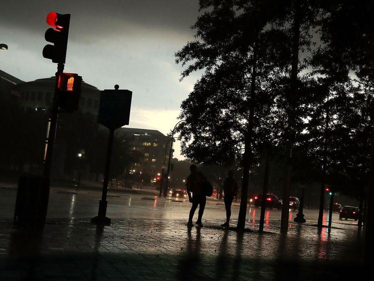 Des gens se tiennent sous les arbres alors qu'un violent orage survient au Capitole à Washington DC