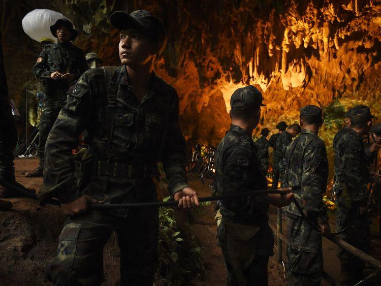 Des soldats thaïlandais relaient un câble électrique dans la grotte de Tham Luang