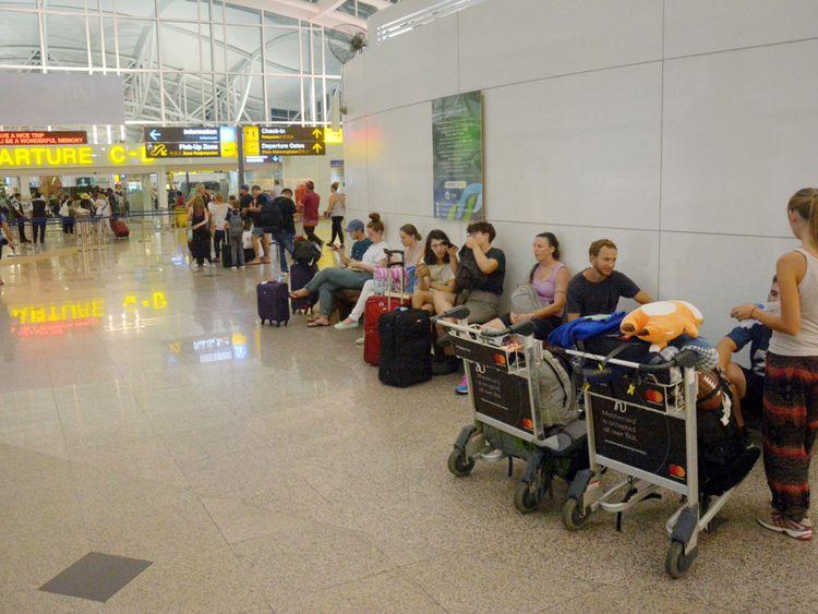 Les passagers sont attendus en attente de vols à l'extérieur du terminal international de l'aéroport Ngurah Rai après ...