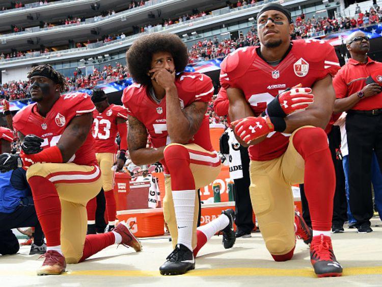 """Colin Kaepernick, au centre, a commencé le kn Colin Kaepernick (C) a commencé le mouvement de protestation agenouillé en 2016 avant le match de la saison </span><br />       </figcaption></figure> </div> <p> Les protestations de la NFL ont commencé en 2016 lorsque le quarterback des San Francisco 49ers Colin Kaepernick a commencé </p> <p> La manifestation de Kaepernick visait à sensibiliser le public au racisme systémique et au meurtre d'hommes noirs par la police. </p> <p> La saison dernière, le vice-président Mike Pence a quitté un match de la NFL après Une douzaine de joueurs ont pris un genou pendant l'hymne </p> <p> M. Trump a à plusieurs reprises dénoncé la protestation des joueurs, les qualifiant de """"fils de pute"""" qui devraient être renvoyés. </p> <p> Le mois dernier, la NFL annonçait une nouvelle politique exigeant des joueurs pour représenter l'hymne s'ils sont sur le terrain avant un match. </p> <div class="""