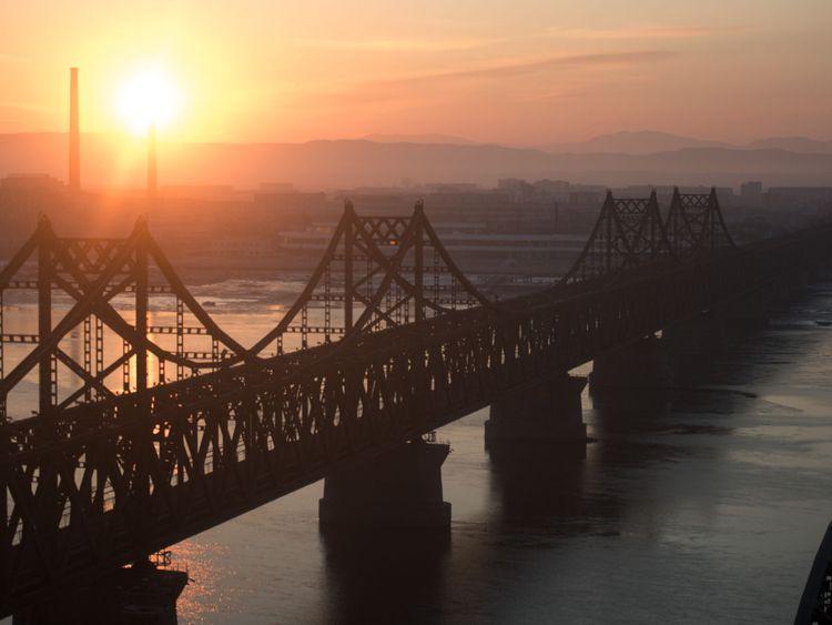Le soleil se lève sur le pont sur les rives de la rivière Yalu dans la ville frontalière chinoise de Dandong, en face de la ville nord-coréenne de Sinuiju, le 10 février 2016