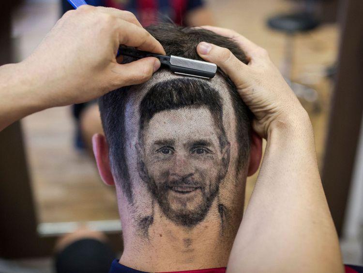 Un fan de football arbore un tatouage de cheveux montrant le portrait du footballeur argentin Lionel Messi