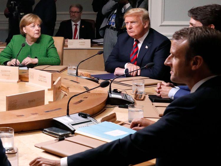 La chancelière allemande Angela Merkel regarde le président américain Donald Trump avec le Premier ministre du Canada Justin Trudeau, le président de la France Emmanuel Macron et les autres dirigeants pour une séance plénière au sommet du G7 à Charlevoix, Québec, Canada, le 8 juin 2018. REUTERS / Leah Millis