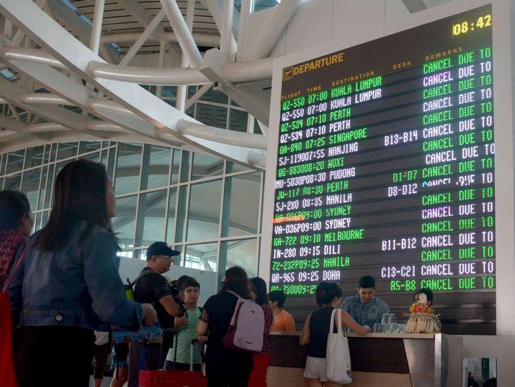 Les voyageurs vérifient leurs vols à l'aéroport Ngurah Rai de Denpasar, Bali, qui est fermé le 29 juin 2018 après qu'un rapport pilote ait détecté des cendres volcaniques s'élevant jusqu'à 23 000 pieds après l'éruption du Mont Agung. - Bali a fermé son aéroport international à la suite d'une éruption volcanique sur l'île de villégiature indonésienne qui a provoqué l'émission de fumée et de cendres épaisses de 2 000 mètres (6 500 pieds) dans l'atmosphère, a indiqué un responsable. (Photo par GEDE ARDIASA / AFP) (Crédit photo devrait lire GEDE ARDIASA / AFP / Getty Images)