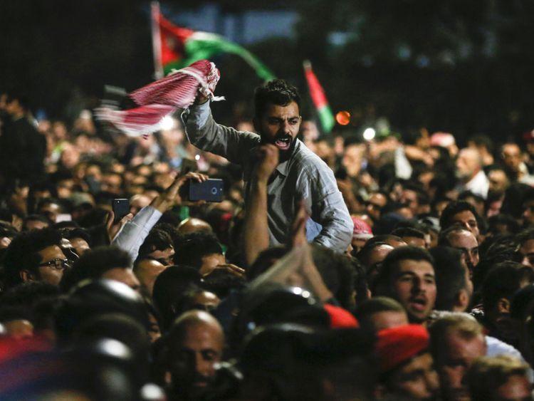 Les manifestants jordaniens crient des slogans et brandissent un drapeau national lors d'une manifestation
